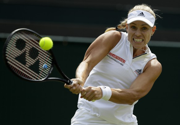 Angelique Kerber of Germany returns the ball to Belinda Bencic of Switzerland during their women's singles match on the seventh day at the Wimbledon Tennis Championships in London, Monday July 9, 2018. (AP Photo/Kirsty Wigglesworth)