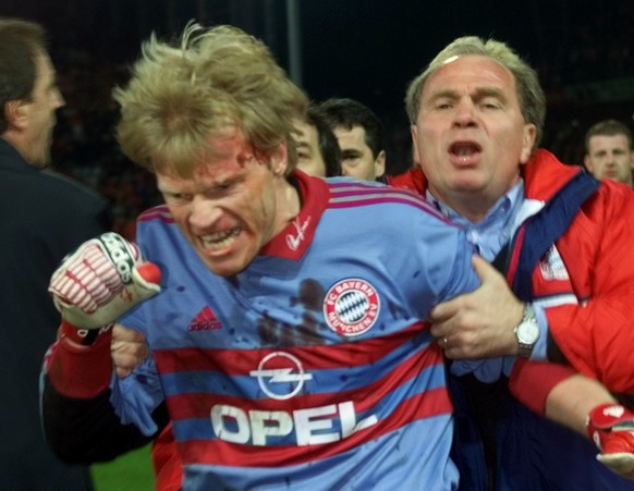 Bayern Munich's manager Uli Hoeness, right, holds bleeding goalkeeper Oliver Kahn at the end of the German soccer first league match SC Freiburg versus Bayern Munich in Freiburg's Dreisam stadium, Wednesday, April12, 2000. Kahn was angry after he was hit by an object thrown by spectators shortly before the end of the match. Munich won 2-1. (KEYSTONE/AP Photo/Thomas Kienzle)