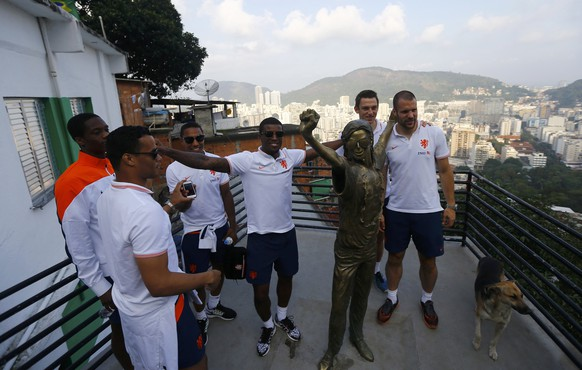"""Netherlands' national soccer team players pose with a statue of the late pop star Michael Jackson during a visit to the Santa Marta slum in Rio de Janeiro, July 1, 2014. The statue was placed in the area where Jackson filmed part of the Brazilian version of the """"They Don't Care About Us"""" music video in 1995.  REUTERS/Ricardo Moraes (BRAZIL  - Tags: SPORT SOCCER WORLD CUP SOCIETY POVERTY ENTERTAINMENT)"""