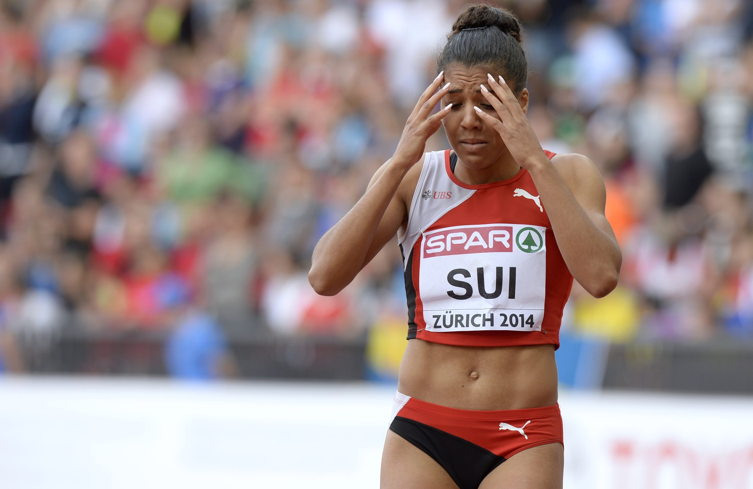Switzerland's Mujinga Kambundji reacts after she lost the baton at the start, of the women's 4x100m relay round 1 race, at the sixth day of the European Athletics Championships in the Letzigrund Stadium in Zurich, Switzerland, Sunday, August 17, 2014. (KEYSTONE/Steffen Schmidt)