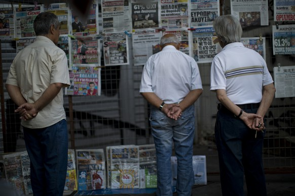 """People look at the newspapers at a newsstand in central Athens, Monday, July 6, 2015. Greece's finance minister has resigned following Sunday's referendum in which the majority of voters said """"no"""" to more austerity measures in exchange for another financial bailout. (AP Photo/Emilio Morenatti)"""