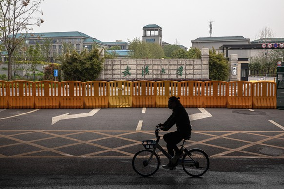 epa08338268 A man wearing a protective face mask rides a bicycle next to a security fence surrounding territory of Wuhan University, in Wuhan, China, 02 April 2020. Many students in Wuhan's universities are still being lockdown and cannot leave the territories of their universities. Wuhan, the epicenter of the coronavirus outbreak, partly lifted the lockdown allowing people to enter the city after more than two months. According to Chinese government figures over 2,500 people have died of Covid-19 disease caused by the SARS-CoV-2 coronavirus in Wuhan since the outbreak began.  EPA/ROMAN PILIPEY