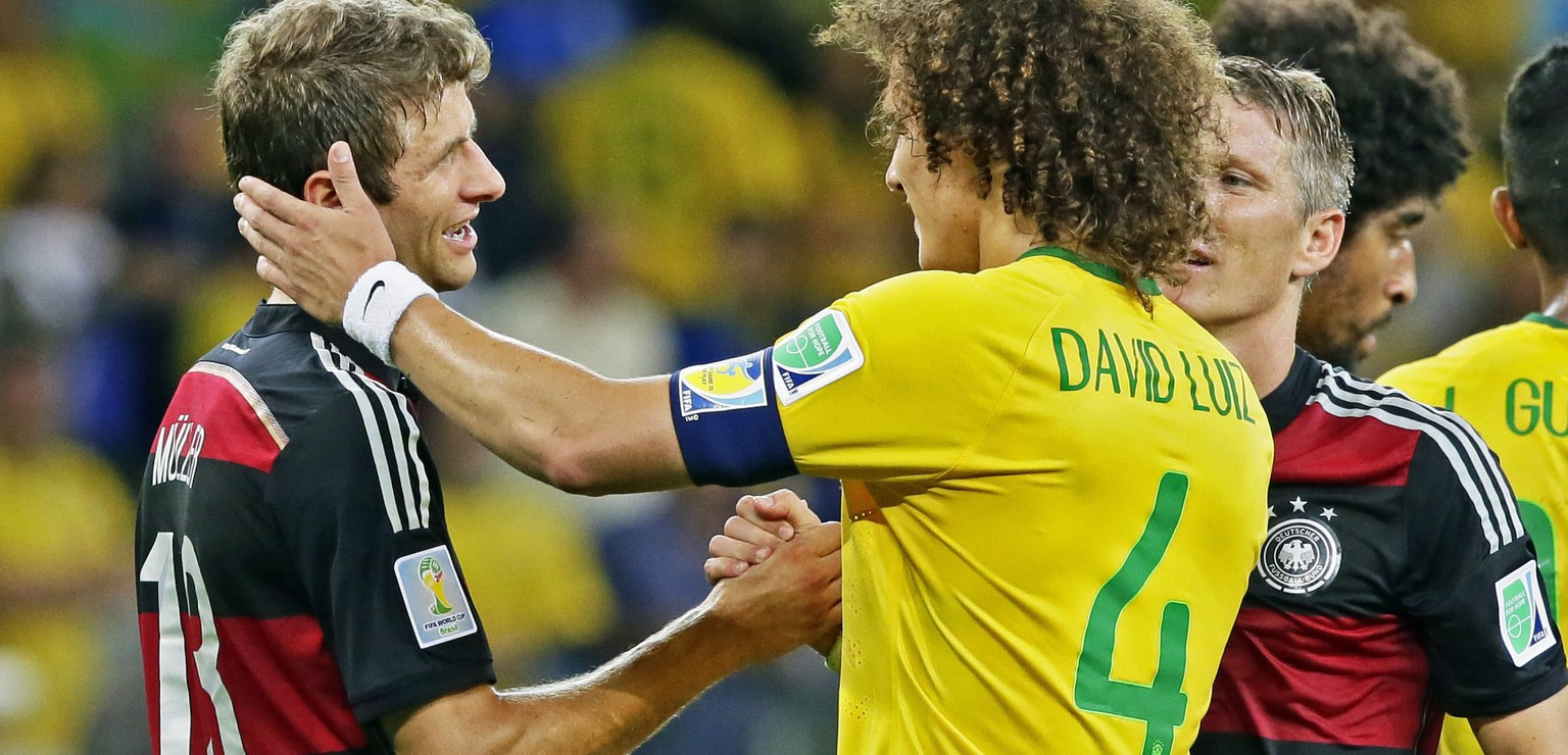 epa04306456 Germany's Thomas Mueller (L) and Brazil's David Luiz (2-R) hug as Germany's Bastian Schweinsteiger (C) walks satisfied after winning the FIFA World Cup 2014 semi final match between Brazil and Germany at the Estadio Mineirao in Belo Horizonte, Brazil, 08 July 2014. 