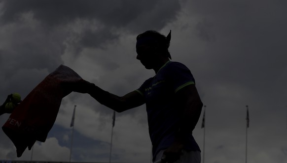 Spain's Rafael Nadal is silhouetted as he gets a towel while playing Georgia's Nikoloz Basilashvili during their third round match of the French Open tennis tournament at the Roland Garros stadium, Friday, June 2, 2017 in Paris. (AP Photo/Petr David Josek)