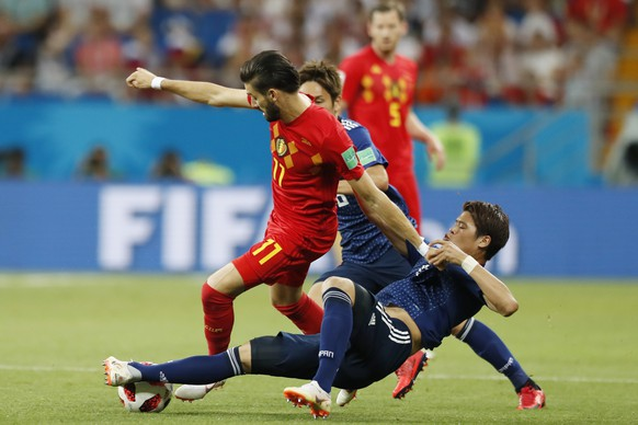 Belgium's Yannick Carrasco battles for the ball with Japan's Hiroki Sakai, bottom, during their round of 16 match at the 2018 soccer World Cup in the Rostov Arena, in Rostov-on-Don, Russia, Monday, July 2, 2018. (AP Photo/Pavel Golovkin)