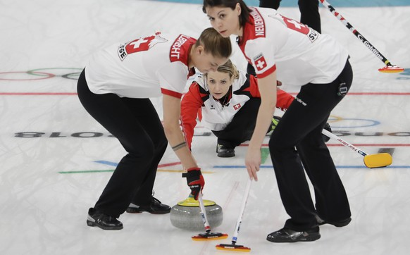 Switzerland's skip Silvana Tirinzoni,center, throws a stone during a women's curling match against Canada at the 2018 Winter Olympics in Gangneung, South Korea, Sunday, Feb. 18, 2018. (AP Photo/Natacha Pisarenko)