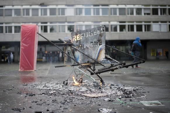 """Ein Einkaufswagen brennt am Helvetiaplatz, nach dem traditionellen 1. Mai-Umzug am Tag der Arbeit, in Zuerich, am Sonntag, 1. Mai 2016. Der Tag der Arbeit steht dieses Jahr im Zeichen der AHV. Die Gewerkschaften stellen den 1. Mai unter das Motto """"Gemeinsam kaempfen - fuer eine starke AHV"""". Der Slogan des Zuercher 1. Mai-Komitees heisst zudem """"Wir sind alle Fluechtlinge"""". (KEYSTONE/Ennio Leanza)"""