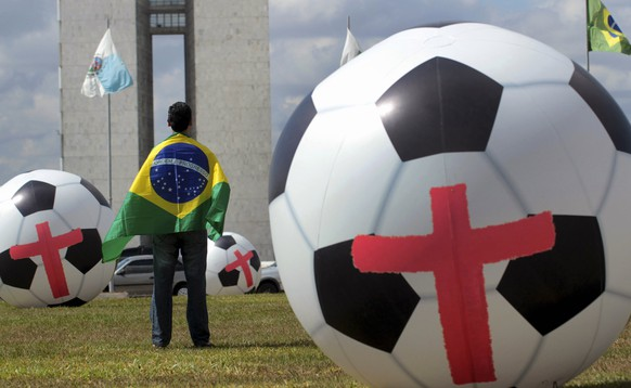 A man stands next to giant inflatable soccer balls marked with red crosses placed by members of non-governmental organization (NGO) Rio de Paz (Rio Peace) during a protest in front of the National Congress in Brasilia June 3, 2014. According to the organization, the protest was a call to the Brazilian government to provide education, health and public services of the same standards as the FIFA World Cup stadiums. REUTERS/Joedson Alves (BRAZIL - Tags: CIVIL UNREST POLITICS SOCIETY SPORT SOCCER WORLD CUP)