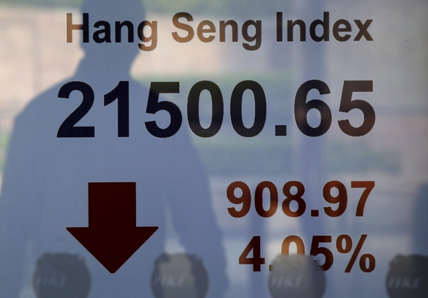 A passerby is reflected on a panel displaying the Hang Seng Index, which drops more than four percent, at the Hong Kong Stocks Exchange in Hong Kong, China August 24, 2015. Asian stocks dived to 3-year lows on Monday as a rout in Chinese equities gathered pace, hastening an exodus from riskier assets as fears of a China-led global economic slowdown roiled world markets. REUTERS/Bobby Yip