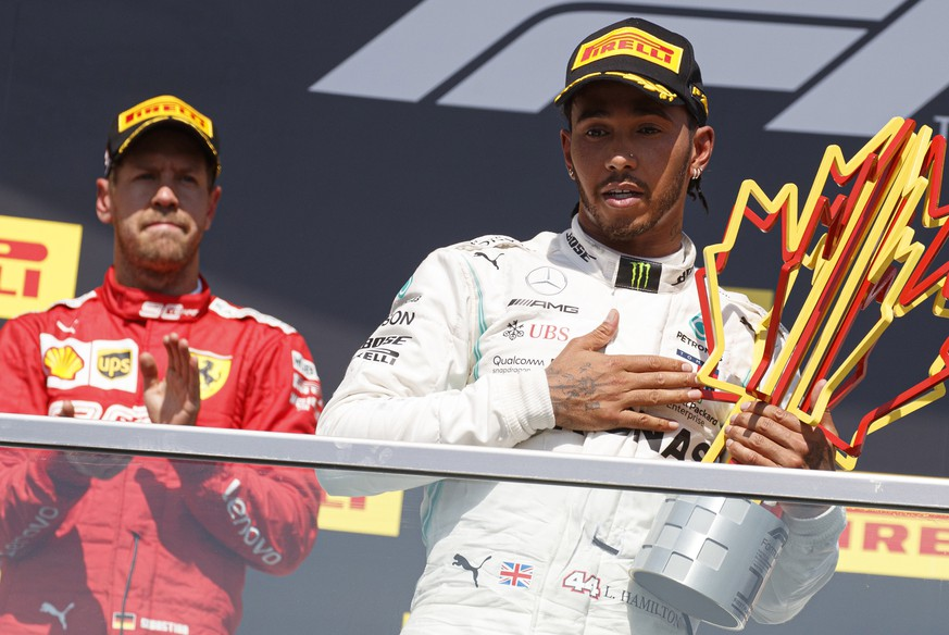 epa07637784 British Formula One driver Lewis Hamilton of Mercedes AMG GP (R) and German Formula One driver Sebastian Vettel of Scuderia Ferrari (L) react on the podium after the 2019 Canada Formula One Grand Prix at the Gilles Villeneuve circuit in Montreal, Canada, 09 June 2019. Hamilton won the 2019 Canada Formula One Grand Prix after Vettel was given a five second penalty leaving him in second place.  EPA/VALDRIN XHEMAJ