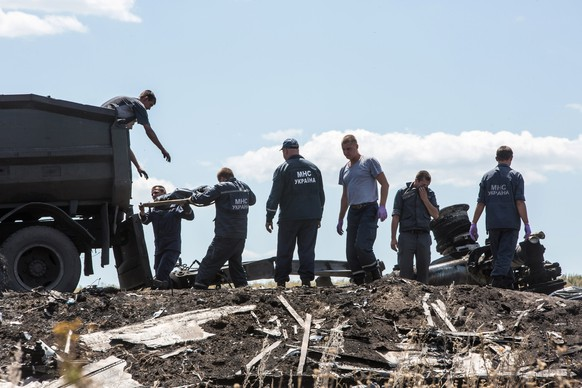 GRABOVO, UKRAINE - JULY 21: Personnel from the Ukrainian Emergencies Ministry load the bodies of victims of Malaysia Airlines flight MH17 into a truck at the crash site on July 21, 2014 in Grabovo, Ukraine.  Malaysia Airlines flight MH17 was travelling from Amsterdam to Kuala Lumpur when it crashed killing all 298 on board including 80 children. The aircraft was allegedly shot down by a missile and investigations continue over the perpetrators of the attack. (Photo by Brendan Hoffman/Getty Images)