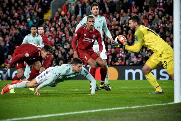epa07381679 Bayern's Robert Lewandowski (C) in action against Liverpool's Roberto Firmino (L) and goalkeeper Alisson (R) during the UEFA Champions League round of 16 first leg soccer match between Liverpool FC and FC Bayern Muenchen at the Anfield in Liverpool, Britain, 19 February 2019.  EPA/PETER POWELL