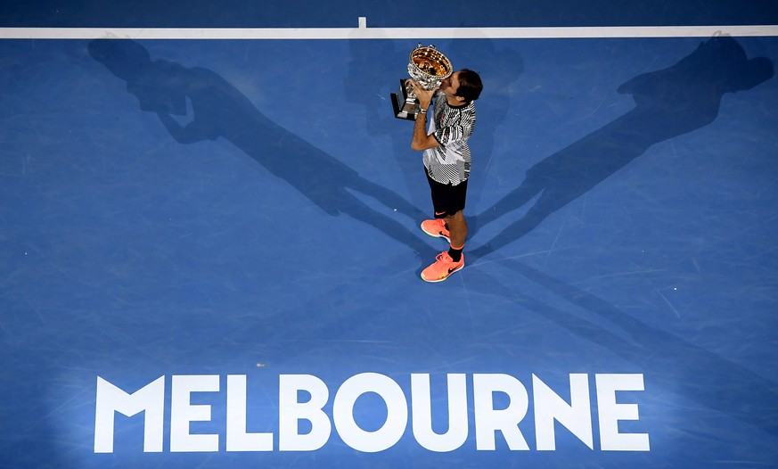 Switzerland's Roger Federer holds his trophy after defeating Spain's Rafael Nadal during the men's singles final at the Australian Open tennis championships in Melbourne, Australia, Sunday, Jan. 29, 2017. (AP Photo/Andy Brownbill)