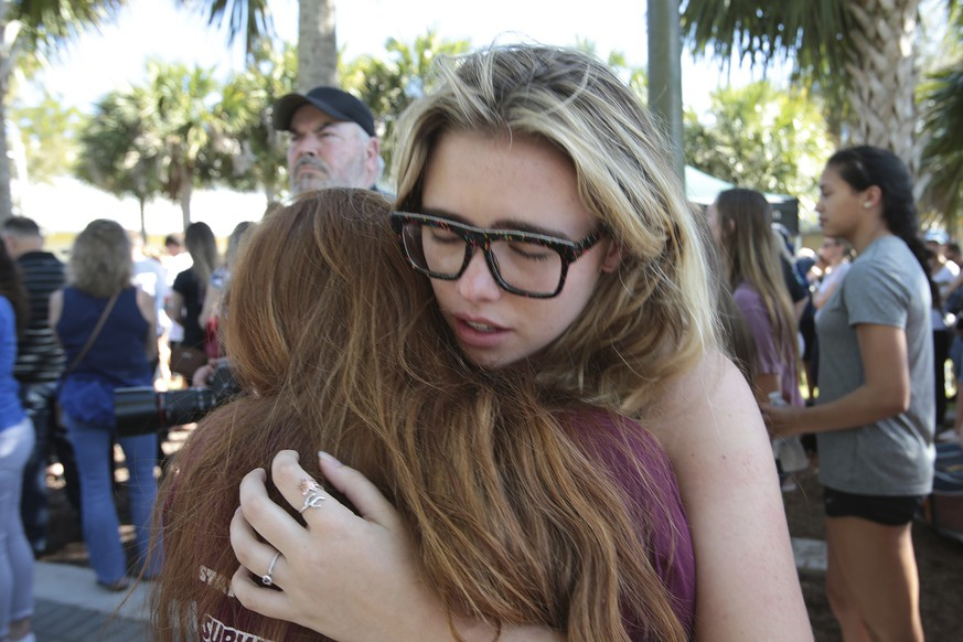 Students console each other outside Pines Trail Center where a candlelight vigil will be held, Thursday, Feb. 15, 2018, in Parkland, Fla. Nikolas Cruz is accused of opening fire Wednesday at Marjory Stoneman Douglas High School in Parkland, Fla., killing more than a dozen people and injuring several. (AP Photo/Joel Auerbach)