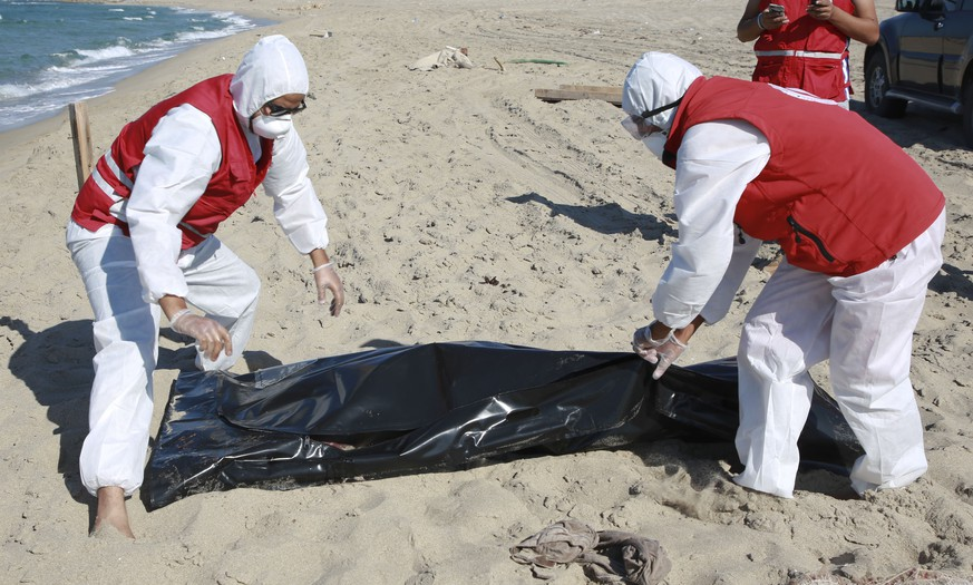 Libyan Red Crescent workers pick up a body of a drowned migrant near the city of Khoms, some 100 kilometers (60 miles) east of Tripoli, Libya, Friday, July 26, 2019. Libya's coast guard recovered dozens of bodies of Europe-bound migrants who perished at sea as search operations continued Friday, a day after up to 150 people, including women and children, went missing and were feared drowned after their boats capsized in the Mediterranean Sea. (AP Photo/Hazem Ahmed)