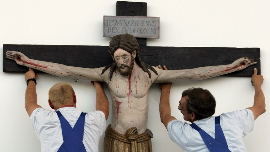 Workers suspend the 1100-year-old crucifix from the church of the village of Enghausen, Bavaria, above the altar on the fair grounds in Munich, southern Germany, Thursday, Sept. 7, 2006, where pope Benedict XVI will celebrate a mass on Sunday, Sept. 10, 2006. The pontiff  will spend six days in his Bavarian homeland from Sept. 9 to Sept. 14, 2006.  The famous Cross of Enghausen, which dates to the year 890  was recently determined to be the oldest life-size crucifix in the world. It will be used during the Mass at the explicit request of Cardinal Friedrich Wetter, Archbishop of Munich. (AP Photo/Diether Endlicher)
