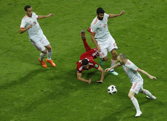 Iran's Mehdi Taremi, center, clashes with Spain's Lucas Vazquez, left, and Spain's Diego Costa, upper right, as Spain's Andres Iniesta picks up the loose ball, during the group B match between Iran and Spain at the 2018 soccer World Cup in the Kazan Arena in Kazan, Russia, Wednesday, June 20, 2018. (AP Photo/Eugene Hoshiko)
