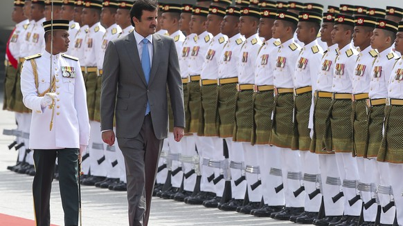 epa06268465 Qatar's Emir Sheikh Tamim bin Hamad al-Thani (C) inspects the honor guard during a welcoming ceremony at the Parliament House in Kuala Lumpur, Malaysia, 16 October 2017. Qatar's Emir Sheikh Tamim bin Hamad al-Thani is on a two-day state visit to Malaysia.  EPA/STR MALAYSIA OUT