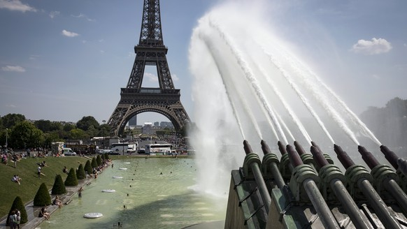 epa06094798 People cool down around the fountain on 'Place du Trocadero' near the Eiffel Tower in Paris, France, 18 July 2017. France is experiencing a heatwave with temperatures reaching over 35 degrees Celsius.  EPA/IAN LANGSDON