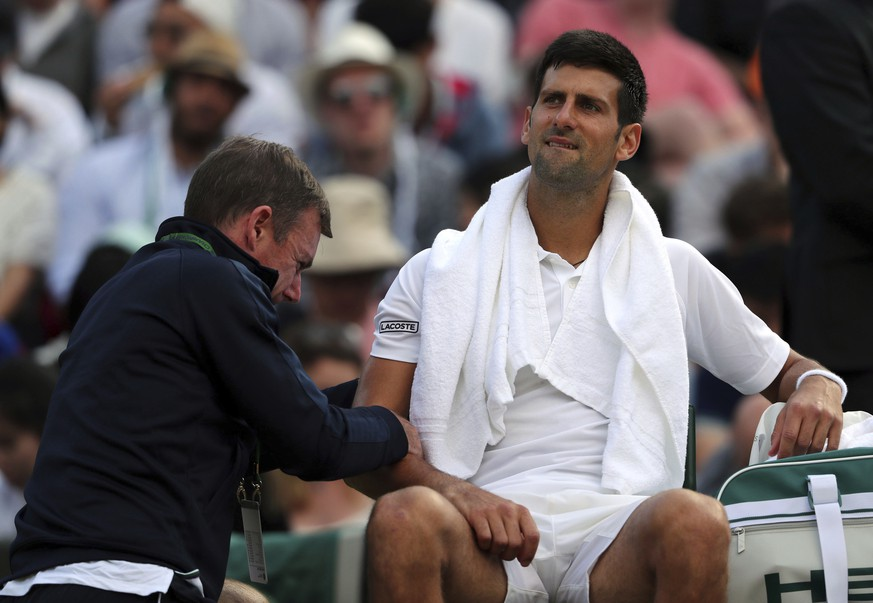 Serbia's Novak Djokovic receives medical treatment during his Men's Singles Match against Czech Republic's Tomas Berdych on day nine of the Wimbledon Tennis Championships at The All England Lawn Tennis and Croquet Club, London, Wednesday, July 12, 2017. (Gareth Fuller/PA via AP)