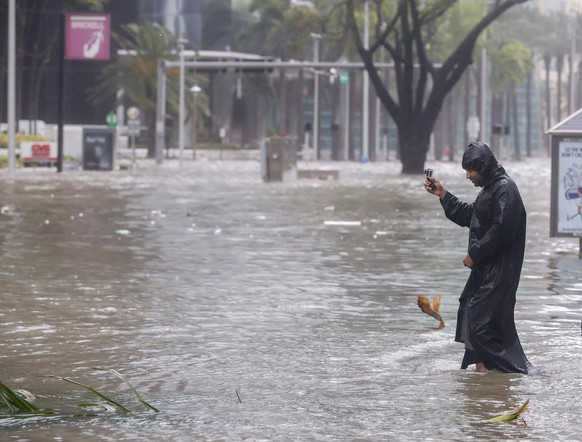 epa06197175 Peter Moodley documents the storm surge flood waters along Brickell Avenue after the full effects of Hurricane Irma struck in Miami, Florida, USA, 10 September 2017. Many areas are under mandatory evacuation orders as Irma Florida.  EPA/ERIK S. LESSER