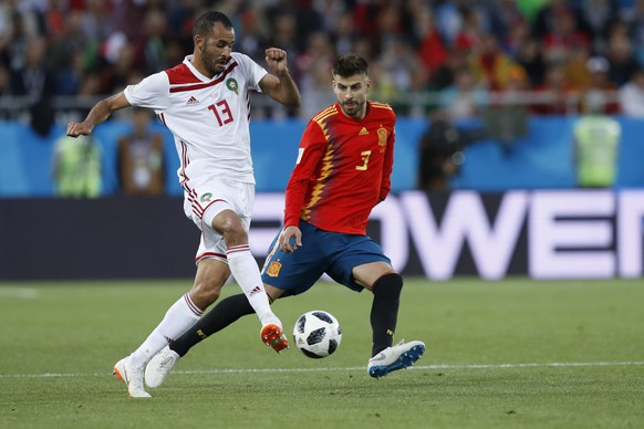 Morocco's Khalid Boutaib, left, and Spain's Gerard Pique challenge for the ball during the group B match between Spain and Morocco at the 2018 soccer World Cup at the Kaliningrad Stadium in Kaliningrad, Russia, Monday, June 25, 2018. (AP Photo/Manu Fernandez)