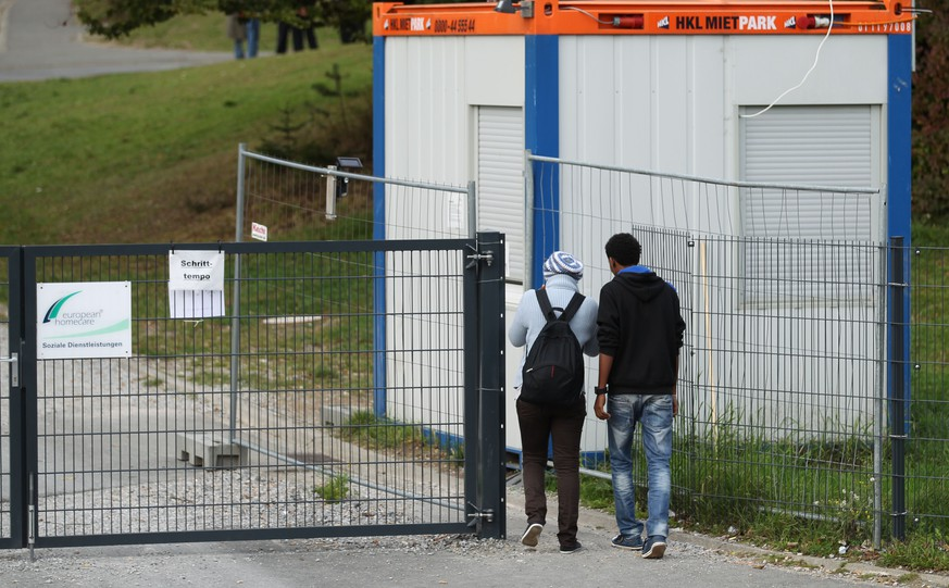 Refugees enter on September 29, 2014 a refugee center created on the site of the former barracks in Burbach, Germany. German police Monday investigated four private security guards accused of abusing and humiliating political asylum seekers in a refugee centre in ways that drew comparisons to conditions in Guantanamo Bay.   AFP PHOTO / DPA / INA FASSBENDER /GERMANY OUT