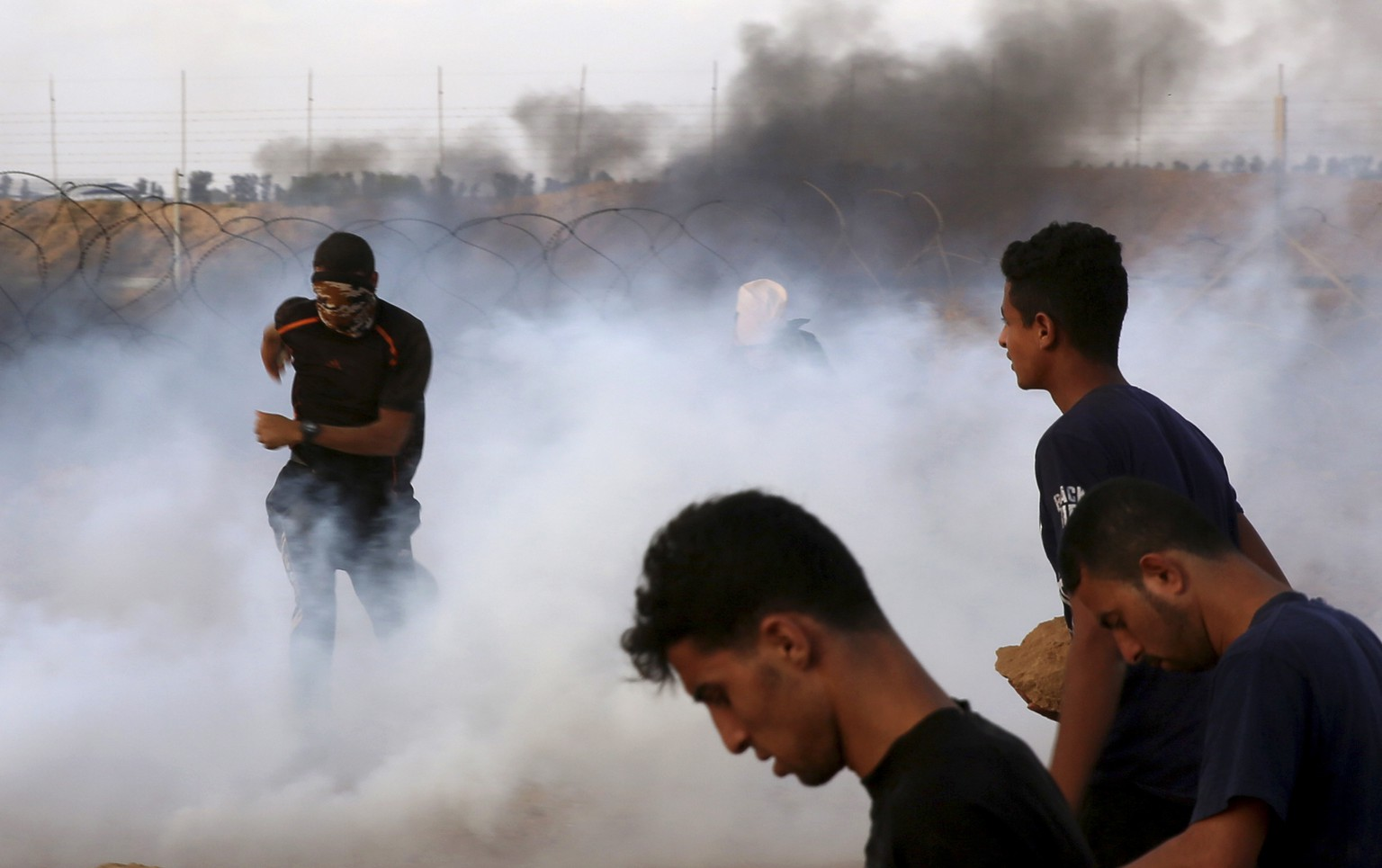 Protesters run for cover from teargas fired by Israeli troops near fence of the Gaza Strip border with Israel, during a protest east of Khan Younis, southern Gaza Strip, Friday, July 20, 2018. Israel targeted Hamas positions in Gaza, killing four Palestinians on Friday in a series of air strikes after gunmen shot at soldiers near the border, officials said. (AP Photo/Adel Hana)