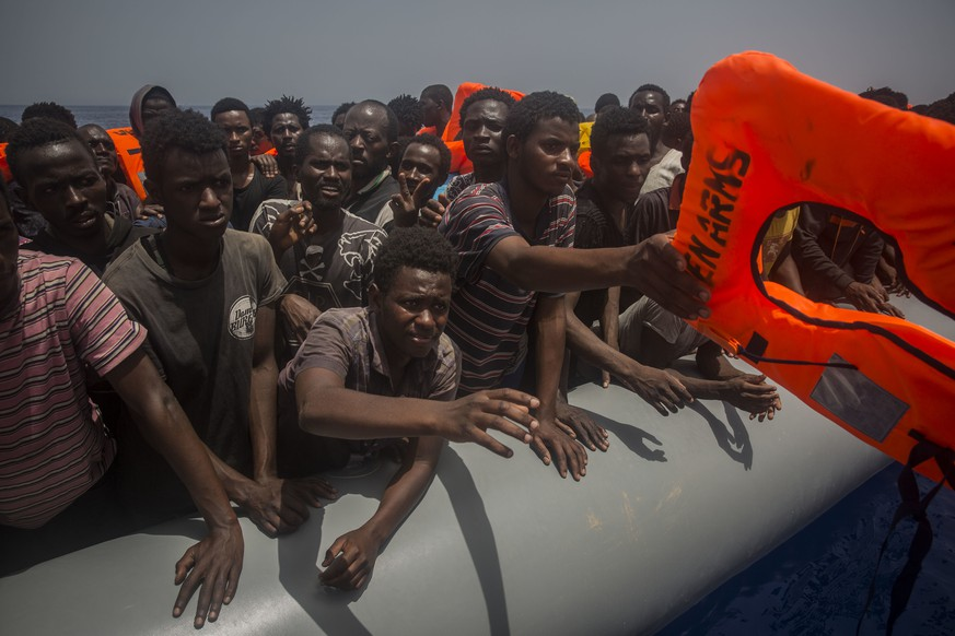 Migrants and refugees receive lifejackets from Spanish NGO Proactiva Open Arms workers, after being located sailing on an out of control rubber boat in the Mediterranean Sea, about 12 miles north of Sabratha, Libya on Sunday, July 23, 2017. (AP Photo/Santi Palacios)