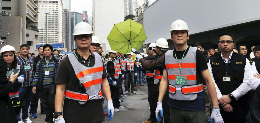 A worker holds an umbrella as he and his coworkers clear an area blocked by pro-democracy protesters near the government headquarters building at the financial Central district in Hong Kong, December 11, 2014. Hong Kong authorities started on Thursday clearing the main pro-democracy protest site that has choked roads into the city's most economically and politically important district for more than two months as part of a campaign to demand free elections.  REUTERS/Tyrone Siu (CHINA - Tags: CIVIL UNREST POLITICS BUSINESS)