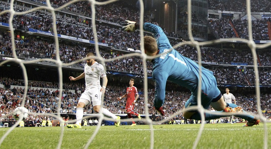 Real Madrid's Karim Benzema (L) scores against Bayern Munich's goalkeeper Manuel Neuer during their Champions League semi-final first leg soccer match at Santiago Bernabeu stadium in Madrid April 23, 2014. REUTERS/Darren Staples (SPAIN  - Tags: SPORT SOCCER TPX IMAGES OF THE DAY)