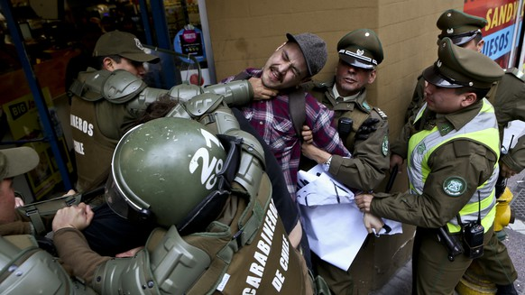 A man is detained by national police outside the Argentina consulate during a protest demanding information on the whereabouts of missing activist Santiago Maldonado, in Santiago, Chile, Thursday, Aug. 17, 2017. Maldonado's family says he went missing Aug. 1, when he was taking part in a protest supporting the land claims by the indigenous Mapuche community. They say border police detained him when he was blocking a road with other protesters in Chubut province, about 1,100 miles (1,800 kilometers) southeast of Argentina's capital. (AP Photo/Esteban Felix)