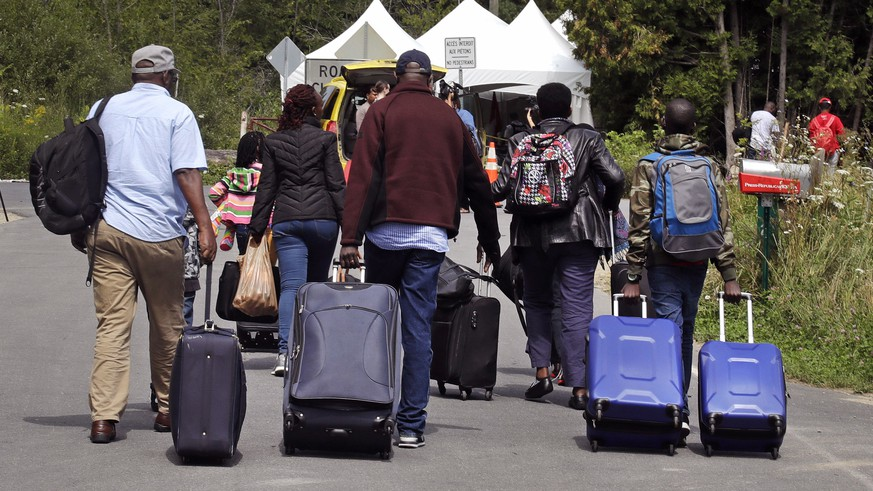 A family from Haiti approach a tent in Saint-Bernard-de-Lacolle, Quebec, stationed by Royal Canadian Mounted Police, as they haul their luggage down Roxham Road in Champlain, N.Y., Monday, Aug. 7, 2017. Officials on both sides of the border first began to notice last fall, around the time of the U.S. presidential election, that more people were crossing at Roxham Road. Since then the numbers have continued to climb. (AP Photo/Charles Krupa)
