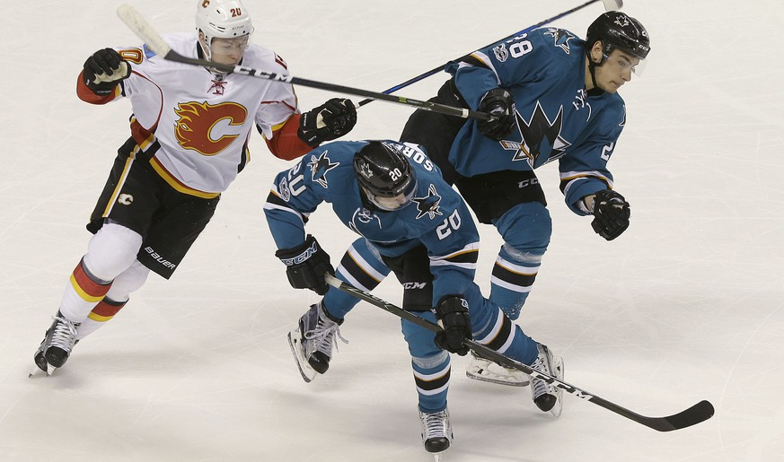 San Jose Sharks right wing Marcus Sorensen, from Sweden, center, tries to control the puck in front of right wing Timo Meier (28), from Switzerland, and Calgary Flames center Curtis Lazar, left, during the first period of an NHL hockey game in San Jose, Calif., Saturday, April 8, 2017. (AP Photo/Jeff Chiu)