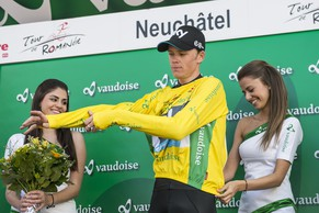 Winner of the 68th Tour de Romandie British Christopher Froome of team Sky Procycling adjusts his yellow jersey with two hostess on the podium during the 5th and last stage, a 18,5 km race against the clock, at the 68th Tour de Romandie UCI ProTour cycling race, in the Stadium Maladiere in Neuchatel, Switzerland, Sunday, May 4, 2014. (KEYSTONE/Jean-Christophe Bott)