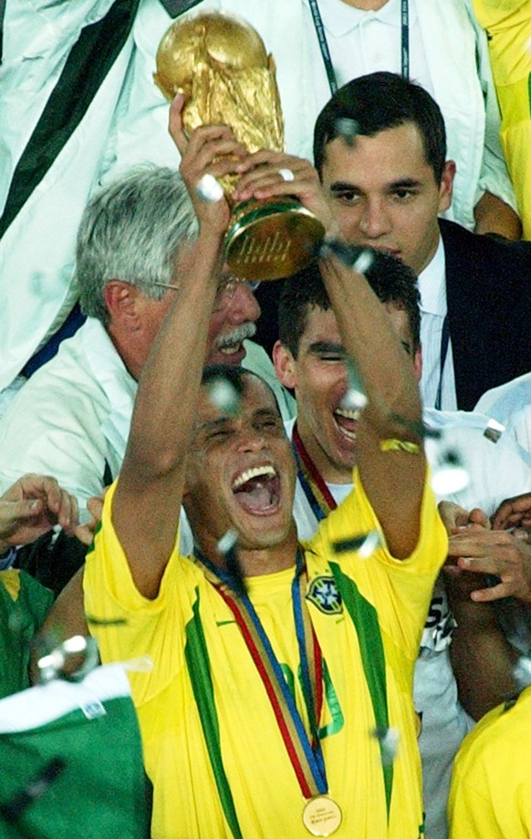"""FILE - In this June 30, 2002 file photo, Brazil's Rivaldo celebrates with the World Cup trophy after defeating Germany 2-0 in the 2002 World Cup final, in Yokohama, Japan. The former Brazil and Barcelona star Rivaldo officially retired on Saturday, March 15, 2014, after a 24-year career that he said was built """"upon a miracle"""" that allowed him to overcome financial challenges and disappointments. (AP Photo/Koji Sasahara, File)"""