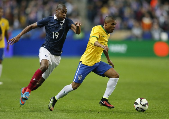 epa04680731 Brazil's Douglas Costa (R) vies for the ball with France's Geoffrey Kondogbia (L) during the international friendly soccer match between France and Brazil at the Stade de France in Saint-Denis, near Paris, France, 26 March 2015.  EPA/IAN LANGSDON