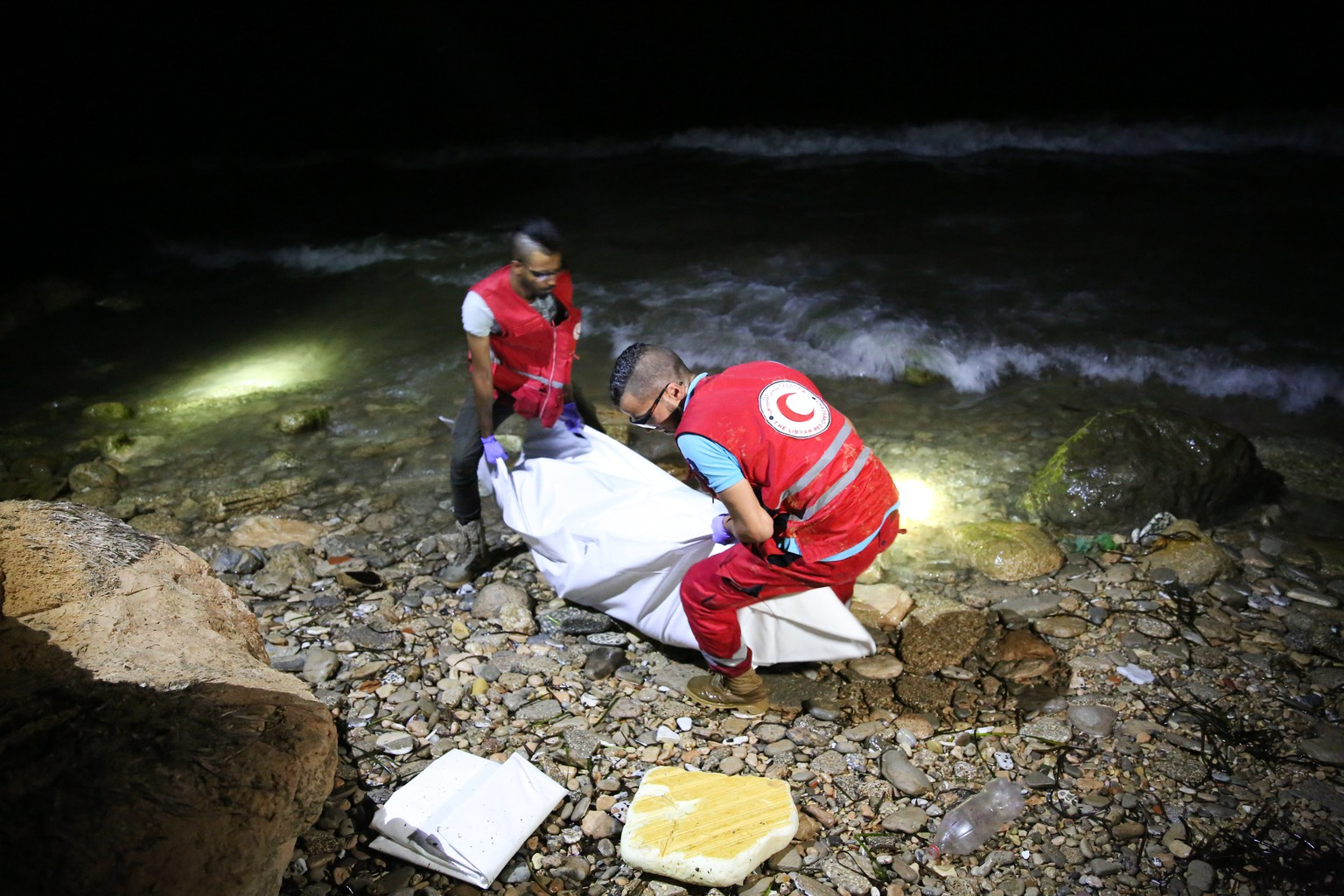 epa06860342 Libyan Red Crescent (LRC) rescue workers carry a body of a drowned migrant on a beach after being washed up, Tajoura, 14 kilometers east of Tripoli, Libya, 02 July 2018 (issued 03 July 2018). According to reports, Libyan rescuers found bodies of 17 drowned migrants over the past two days, after a migrant boat sank off the coast on 29 June with some 100 people missing in the incident.  EPA/STRINGER