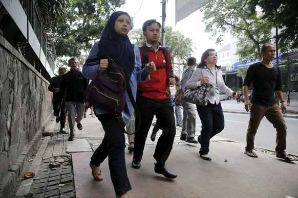 Indonesian workers run as they are evacuated from their office at Thamrin business district in Jakarta January 14, 2016.  Several explosions went off and gunfire broke out in the center of the Indonesian capital on Thursday and police said they suspected a suicide bomber was responsible for at least one the blasts.  REUTERS/Beawiharta