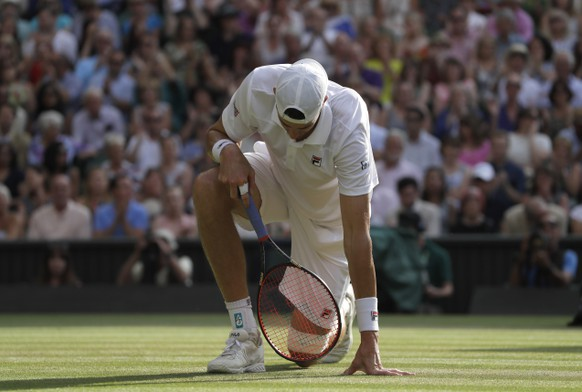 John Isner of the United States kneels after stumbling as he returned the ball to South Africa's Kevin Anderson during their men's singles semifinals match at the Wimbledon Tennis Championships, in London, Friday July 13, 2018.(AP Photo/Kirsty Wigglesworth)