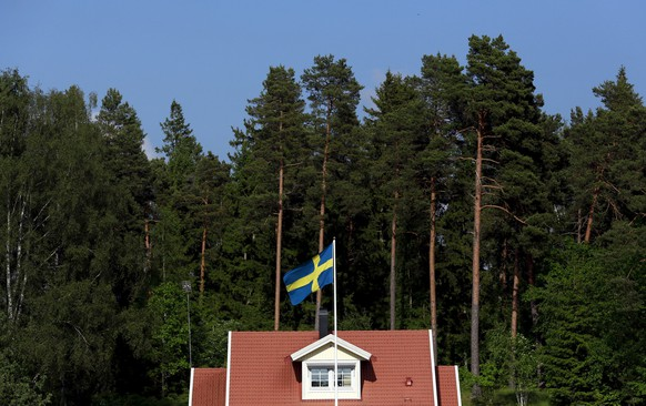 A Swedish national flag flies in front of a house near the town of Sodertalje, southwest of Stockholm, Sweden, in this file picture taken June 5, 2014. A housing shortage has sharply pushed up property prices in Sweden as well as in Norway and inflated Nordic household debt to the highest levels in the OECD. There are fears that a housing bubble could endanger financial stability in the region. With more than a million refugees arriving in Europe over the last year, Sweden has struggled to reconcile one of the fastest growing populations in the European Union with some of the highest construction costs.    REUTERS/Cathal McNaughton/Files