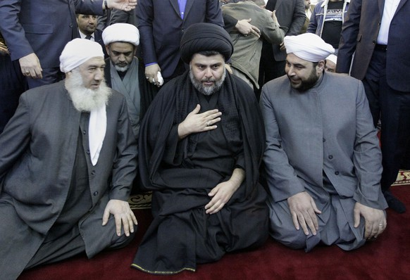 FILE - In this Jan. 4, 2013 file photo, Shiite cleric Muqtada al-Sadr, center, is welcomed by Sunni clerics at Abdul-Qadir al-Gailani Sunni mosque in Baghdad, Iraq. Al-Sadr, who led punishing attacks on American forces after the 2003 U.S.-led overthrow of Saddam Hussein, appears set to secure the most significant victory of his political career with a strong showing in the May 12 parliamentary election. Al-Sadr gained popularity as a nationalist voice campaigning against corruption and against Iran's influence in the country. (AP Photo/Khalid Mohammed, File)