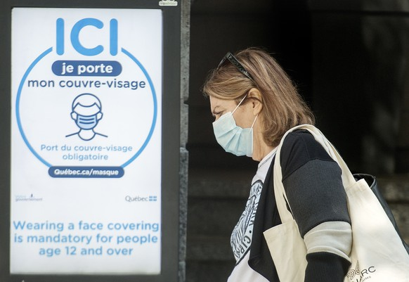 A woman wears a face mask as she walks by a sign advising of the mandatory wearing of masks and face coverings in Montreal, Monday, September 21, 2020, as the COVID-19 pandemic continues in Canada and around the world. (Graham Hughes/The Canadian Press via AP)