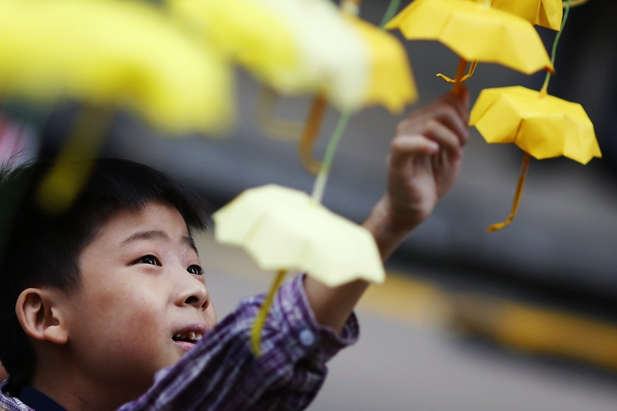 A boy plays with miniature paper umbrellas, the symbol of pro-democracy protesters, at their barricade at the Mongkok shopping district in Hong Kong October 25, 2014. Hong Kong protesters plan to hold a straw poll on government proposals they rejected earlier in the week as their street campaign pushing for democracy for the Chinese-controlled city entered its fifth week on Friday.    REUTERS/Damir Sagolj (CHINA - Tags: POLITICS CIVIL UNREST TPX IMAGES OF THE DAY)