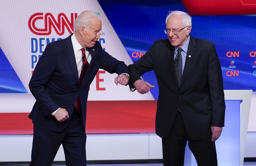 Former Vice President Joe Biden, left, and Sen. Bernie Sanders, I-Vt., right, greet one another before they participate in a Democratic presidential primary debate at CNN Studios in Washington, Sunday, March 15, 2020. (AP Photo/Evan Vucci) Joe Biden,Bernie Sanders