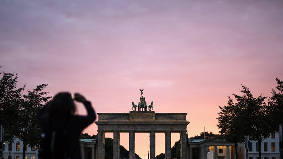 epa06214313 A person takes a photo in front of the Brandenburg Gate landmark during a sunset colored sky in Berlin, Germany, 19 September 2017. In the northern hemisphere, summer ends with 21 September 2017. Autumn begins on 22 September 2017.  EPA/CLEMENS BILAN