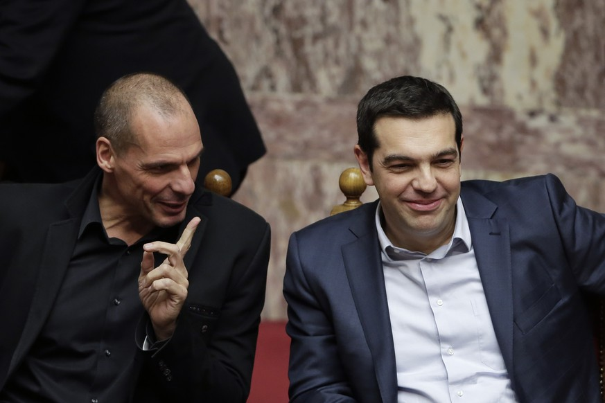 Greece's Prime Minister Alexis Tsipras, right, and Finance Minister Yanis Varoufakis chat during a Presidential vote in Athens, on Wednesday, Feb. 18, 2015. Greece's parliament elected Prokopis Pavlopoulos, a conservative law professor and veteran politician Wednesday as the country's new president, after he received support from the new left-wing government and main center-right opposition party. (AP Photo/Petros Giannakouris)