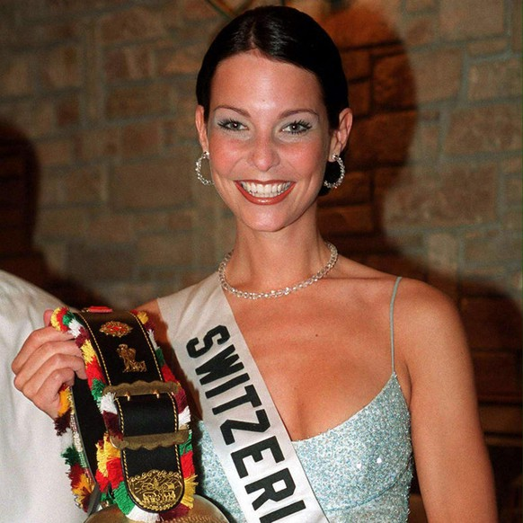 Miss Switzerland Anita Buri holding her gift, a typical cow-bell, in the lobby of the Hilton hotel in Nicosia late Tuesday evening May 2, 2000, during the national gifts auction event of the current 'Miss Universe' competition. Each of the 79 Miss Universe contestants contributed a small gift symbolizing the culture of their respective countries for an auction. The Miss Universe 2000 title will be announced on 13th of May.(KEYSTONE/EPA PHOTO/CNA/GEORGE/CONSTANTINOU)