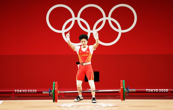 epa09361021 Hou Zhihui of Cina celebrates after an attempt in the Group A Women's 49kg - Snatch during the Weightlifting events of the Tokyo 2020 Olympic Games at the Tokyo International Forum in Tokyo, Japan, 24 July 2021.  EPA/RITCHIE B. TONGO