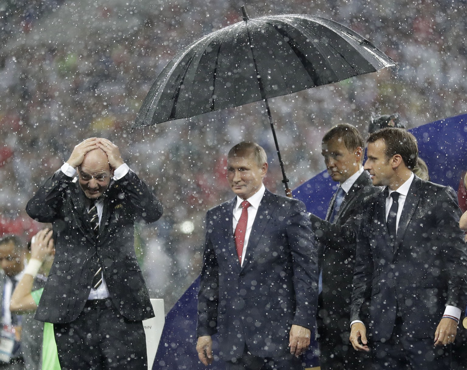 FIFA President Gianni Infantino, left, gestures as Russian President Vladimir Putin stands underneath an umbrella watched by French President Emmanuel Macron after the final match between France and Croatia at the 2018 soccer World Cup in the Luzhniki Stadium in Moscow, Russia, Sunday, July 15, 2018. France won the final 4-2. (AP Photo/Matthias Schrader)